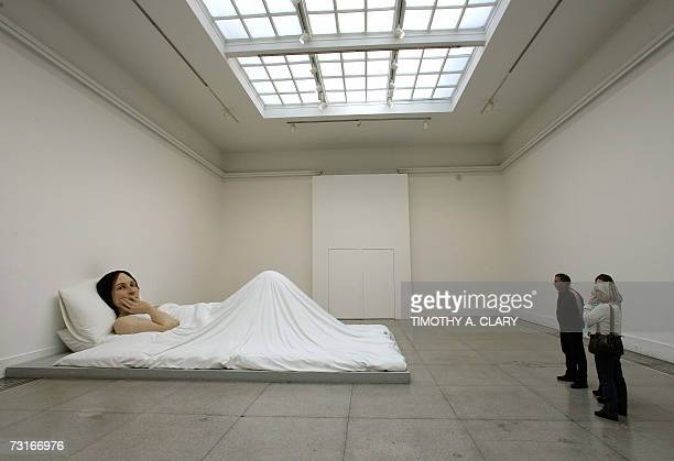 Visitors look at a giant sculpture titled 'In Bed' by Australianborn artist Ron Mueck at the Brooklyn Museum 31 January 2007 Mueck has on exhibit a...