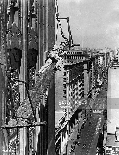 New York USA 27th January 1931 Silent film star Harold Lloyd hanging from a perilously uncomfortable position high above the busy traffic filled road...