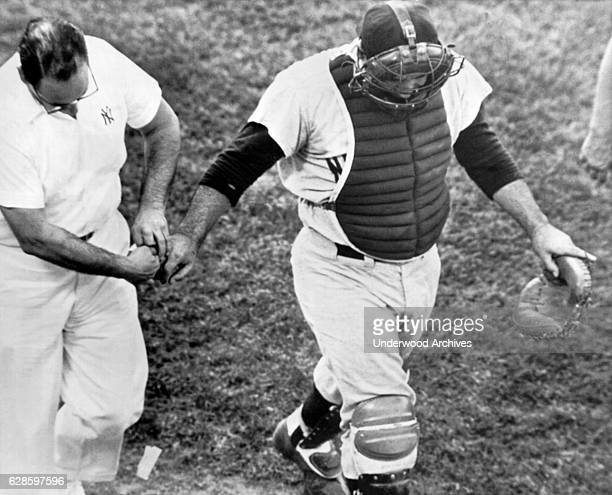New York Yankee catcher Yogi Berra trudges from the field after a foul tip off the bat of Marv Breeding ripped off a finger nail on his right hand...