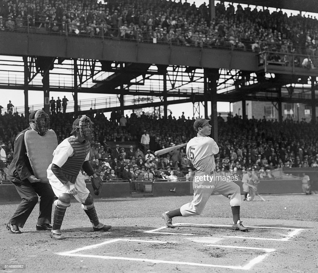 New York Yankee center fielder Joe Dimaggio hits a single in front of Washington catcher Buck Ferrell and Umpire Kolls in the first inning of the...