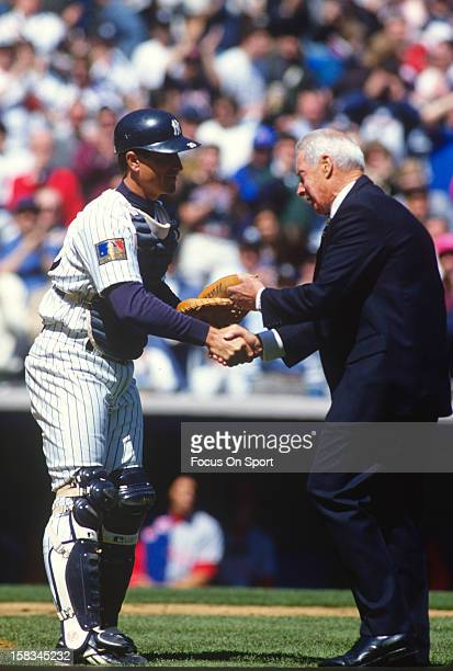 New York Yankee great Joe DiMaggio shakes hands with catcher Mike Stanley after throwing out the ceremonial first pitch before an Major League...