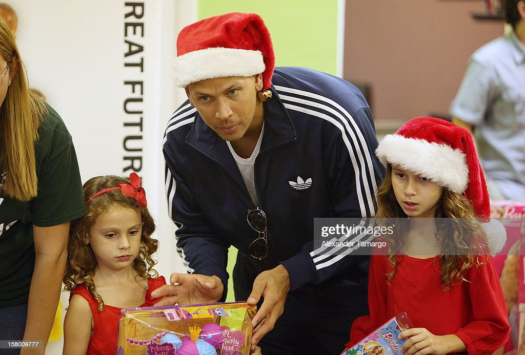 New York Yankees baseball player Alex Rodriguez (C) and his daughters Ella Rodriguez (L) and Natasha Rodriguez (R) help deliver toys at Boys and Girls Club Of Miami-Dade on December 8, 2012 in Miami, Florida.