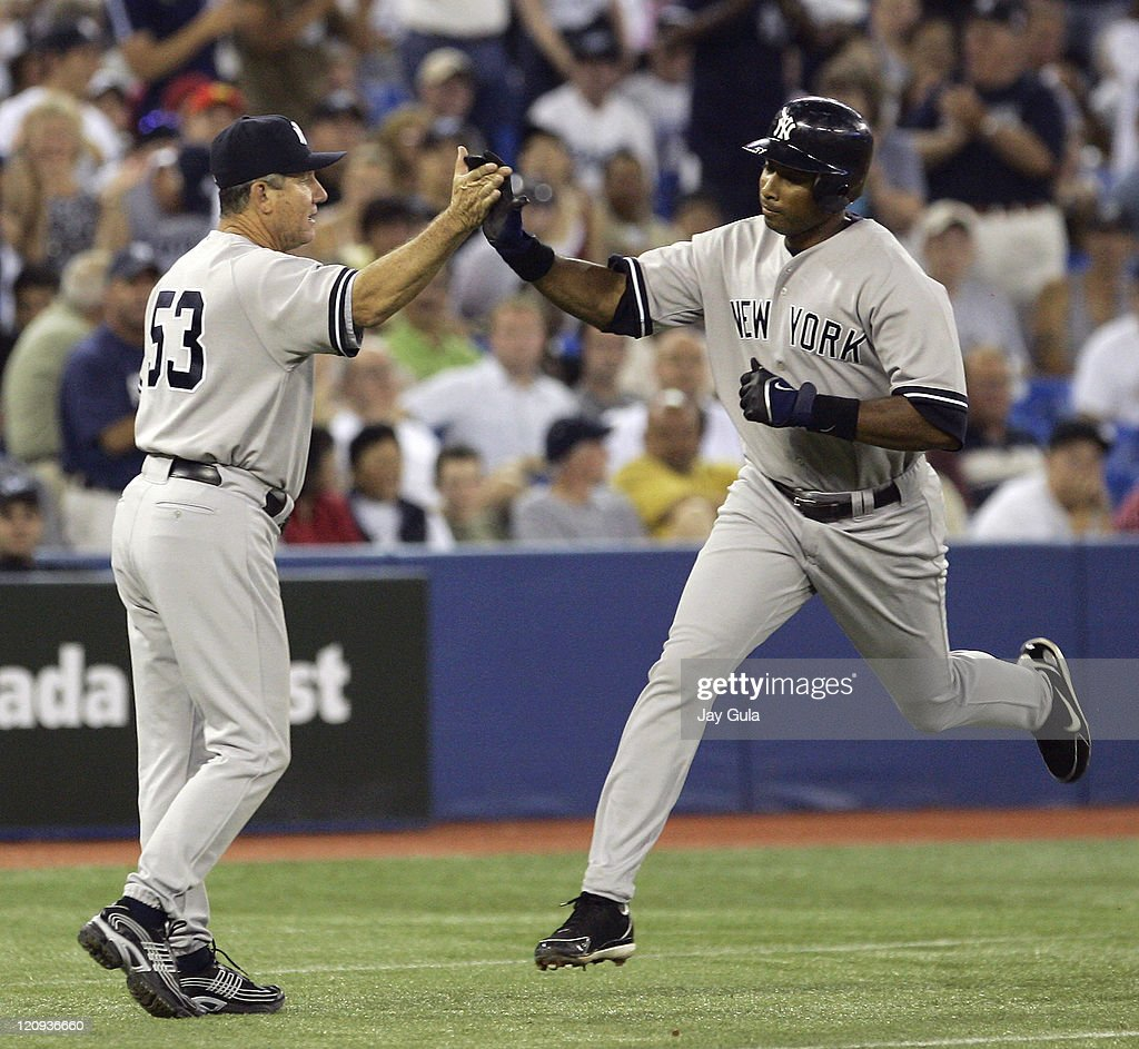 New York Yankees <a gi-track='captionPersonalityLinkClicked' href=/galleries/search?phrase=Bernie+Williams&family=editorial&specificpeople=175814 ng-click='$event.stopPropagation()'>Bernie Williams</a> high fives with third base coach Larry Bowa after hitting his 7th home run of the season against the Toronto Blue Jays at Rogers Centre in Toronto, Canada on July 22, 2006.