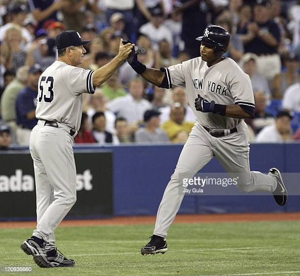 New York Yankees Bernie Williams high fives with third base coach Larry Bowa after hitting his 7th home run of the season against the Toronto Blue...