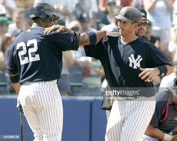 New York Yankees catcher Jorge Posada celebrates with Robinson Cano after hitting a grand slam in a spring training game against the Atlanta Braves...