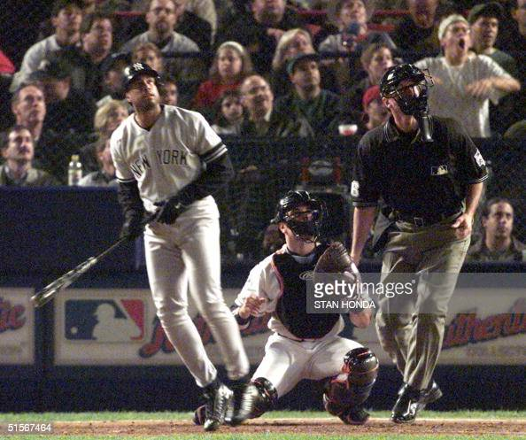 New York Yankees center fielder Bernie Williams watches his home run along with New York Mets catcher Mike Piazza and home plate umpire Tim...