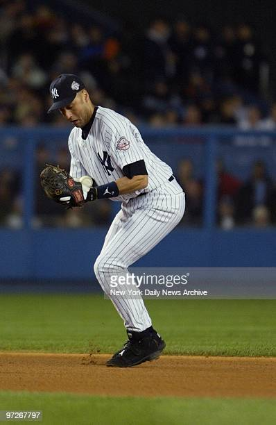 New York Yankees' Derek Jeter bobbles a ball hit by Florida Marlins' Jeff Conine and can't make the play at first base in the sixth inning of Game 6...