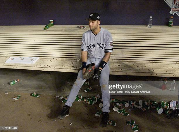 New York Yankees' Derek Jeter sits alone in the dugout as the Arizona Diamondbacks celebrate their 32 win over the Yankees in Game 7 of the World...
