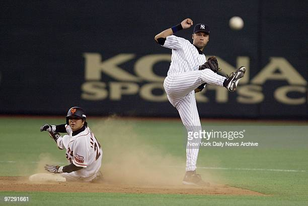 New York Yankees' Derek Jeter turns a double play as Yomiuri Giants' Yoshinobu Takahashi watches from second base during an exhibition game at the...