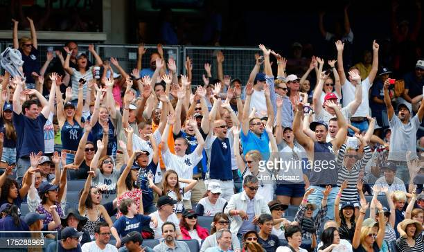 New York Yankees fans doing the 'wave' during a game against the Tampa Bay Rays at Yankee Stadium on July 28 2013 in the Bronx borough of New York...