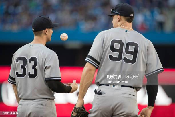 New York Yankees First baseman Greg Bird tosses a ball beside Right fielder teammate Aaron Judge during the regular season MLB game between the New...