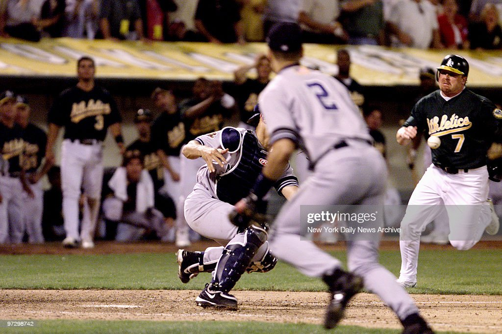 New York Yankees' Jorge Posada holds on to ball after sweep tag on Oakland Athletics' Jeremy Giambi during Game 3 of American League Division Series. Derek Jeter (pictured left) assisted on the play by 'flipping' the ball to Posada after Yankee Shane Spencer's throw from the outfield was off target.
