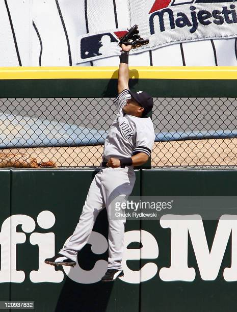 New York Yankees' Left Fielder Melky Cabrera leaps above the left field fence to take a home run away from Juan Uribe during their game versus the...
