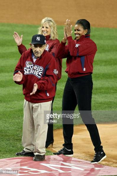 New York Yankees legend and Baseball Hall of Famer Yogi Berra stands on the field with First lady Michelle Obama and Dr Jill Biden wife of Vice...