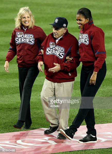New York Yankees legend and Baseball Hall of Famer Yogi Berra walks on the field with First lady Michelle Obama and Dr Jill Biden wife of Vice...