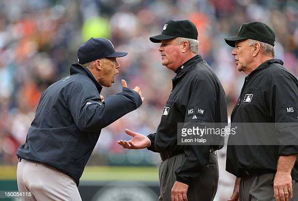 New York Yankees manager Joe Girardi argues with third base umpire Tim Welke and second base umpire Bob Davidson during a disputed call during the...