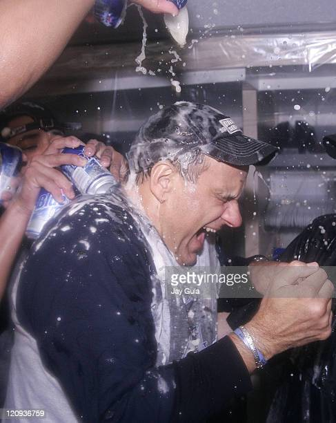New York Yankees manager Joe Torre is doused in champagne as his team celebrates in their clubhouse after clinching their 9th consecutive American...