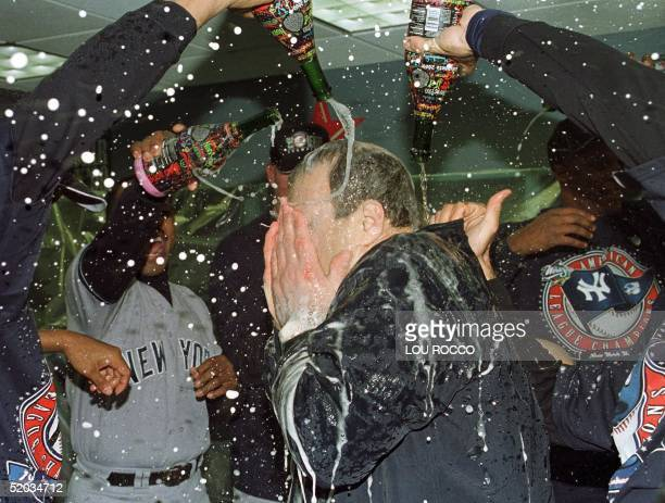 New York Yankees manager Joe Torre is doused with champagne in the locker room after the team's 61 victory over the Boston Red Sox 18 October 1999 at...