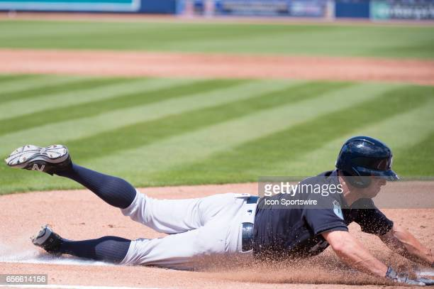 New York Yankees Outfielder Brett Gardner dives and slides into first base after batting during an MLB spring training game between the New York...