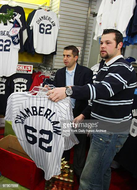 New York Yankees' pitcher Joba Chamberlain holds a jersey with his name and number on it while at the Modell's sporting goods store on W 42nd St...
