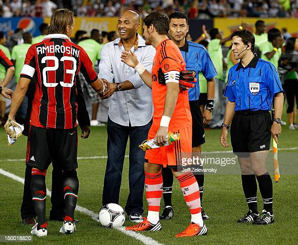 New York Yankees pitcher Mariano Rivera greets Massimo Ambrosini of AC Milan and Iker Casillas of Real Madrid after the coin toss before their match...