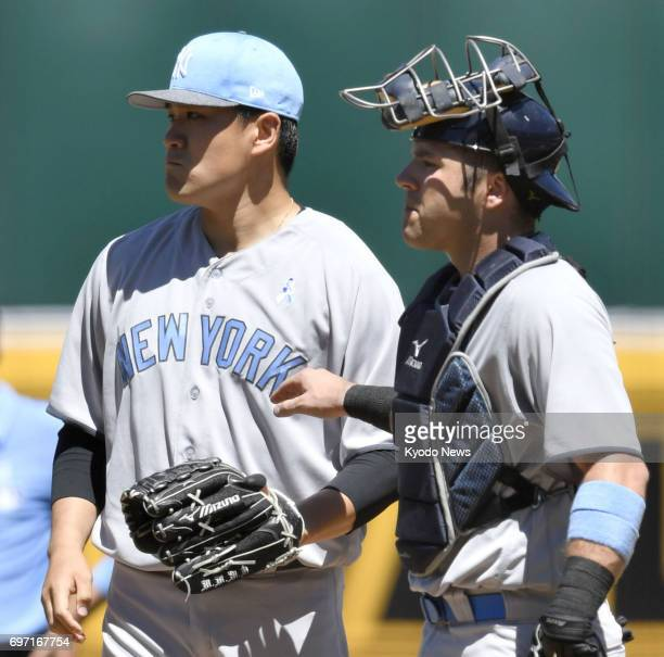 New York Yankees pitcher Masahiro Tanaka and catcher Austin Romine talk during a fourthinning jam against the Oakland Athletics at Oakland Coliseum...