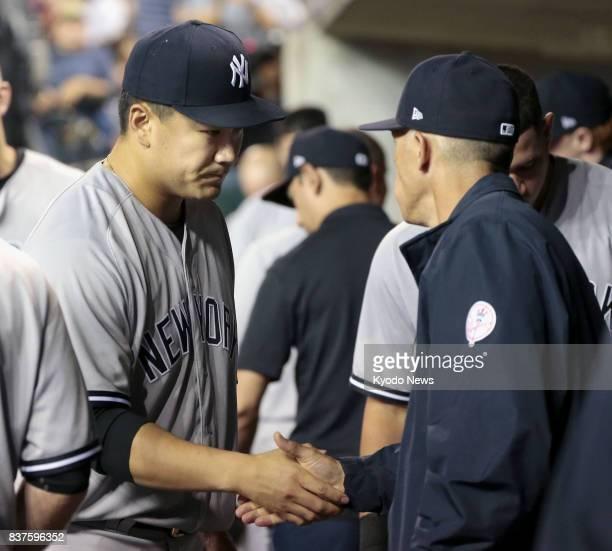 New York Yankees pitcher Masahiro Tanaka and manager Joe Girardi shake hands after Tanaka threw seventh innings against the Detroit Tigers at...