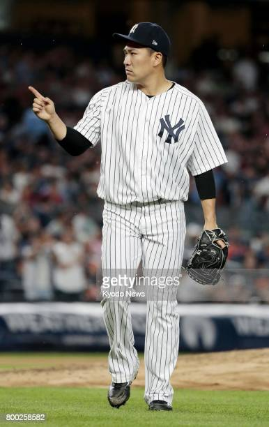 New York Yankees pitcher Masahiro Tanaka walks back to the bench after completing the fifth inning of a game against the Texas Rangers at Yankee...