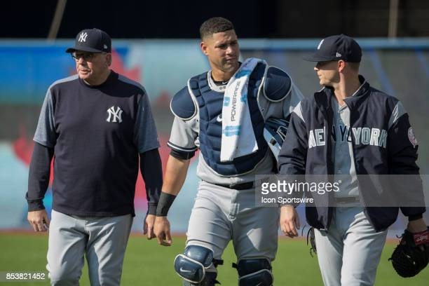 New York Yankees Pitching Coach Larry Rothschild left escorts Catcher Gary Sanchez and starting pitcher Sonny Gray right towards the mound from the...