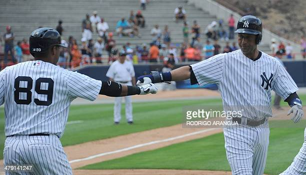 New York Yankees player Derek Jeter is congratulated by his teammate Yangervis Solano after he scored during an exhibition game in Panama City on...