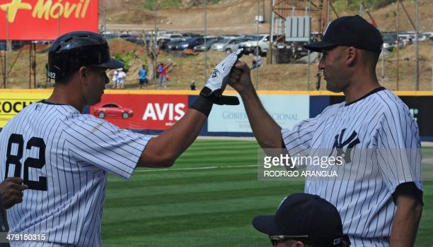 New York Yankees' player Gary Sanchez is congratulated by teammate Derek Jeter after scoring during a Baseball Major League exhibition game against...