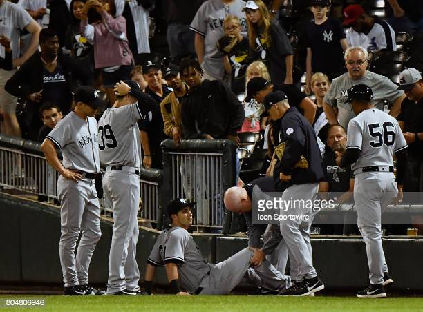 New York Yankees right fielder Dustin Fowler is evaluated by medical staff after injuring his leg chasing down a foul ball during the game between...