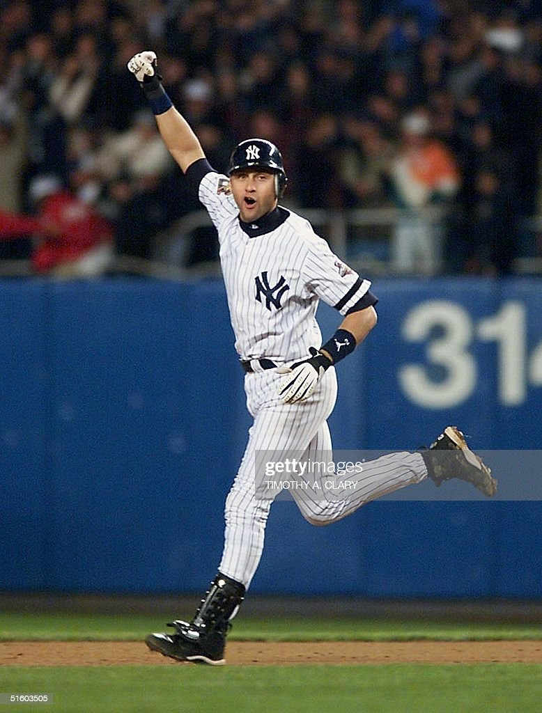 New York Yankees shortstop <a gi-track='captionPersonalityLinkClicked' href=/galleries/search?phrase=Derek+Jeter&family=editorial&specificpeople=167125 ng-click='$event.stopPropagation()'>Derek Jeter</a> celebrates as he rounds the bases during his 10th inning game winning home run during Game 4 of the World Series in Yankee Stadium in New York, 31 October 2001. The Yankees won Game 4 with a score of 4-3 and tied the series with the Arizona Diamondbacks at 2-2. AFP PHOTO/Timothy A. CLARY