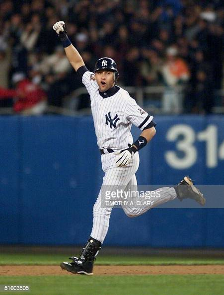 New York Yankees shortstop Derek Jeter celebrates as he rounds the bases during his 10th inning game winning home run during Game 4 of the World...