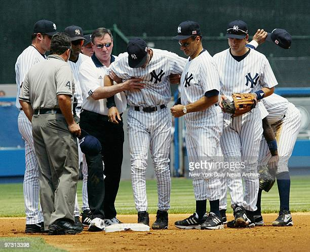 New York Yankees shortstop Derek Jeter is helped off the field by trainer Gene Monahan and manager Joe Torre after a takeout slide at second base...