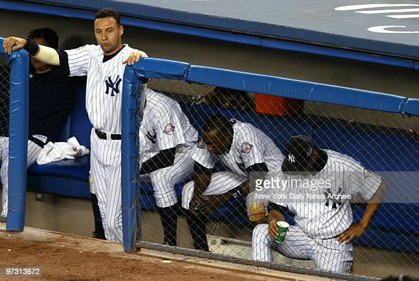 New York Yankees' shortstop Derek Jeter looks out of the dugout as infielder Alfonso Soriano and other teammates hang their heads dejectedly in the...