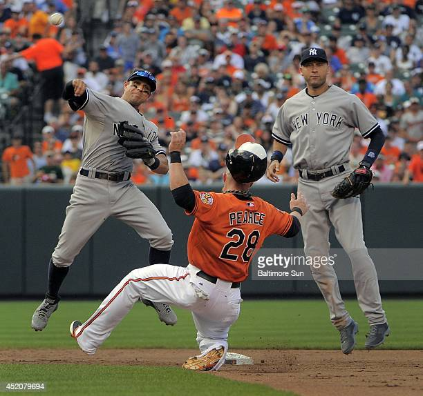New York Yankees shortstop Derek Jeter right watches second baseman Brian Roberts relay a throw over the Baltimore Orioles' Steve Pearce for a double...
