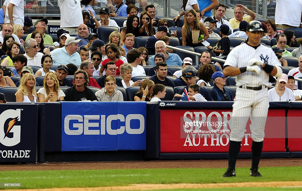 New York Yankees slugger Alex Rodriguez stands at third base as actress Kate Hudson her mother Goldie Hawn and Kurt Russel look on from the stands at...