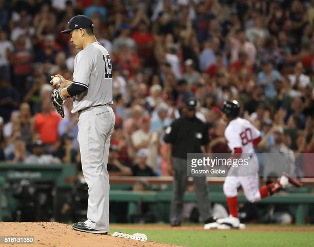 New York Yankees starting pitcher Masahiro Tanaka looks at the ball after Boston Red Sox Mookie Betts rounds third base after hitting a 2run home run...