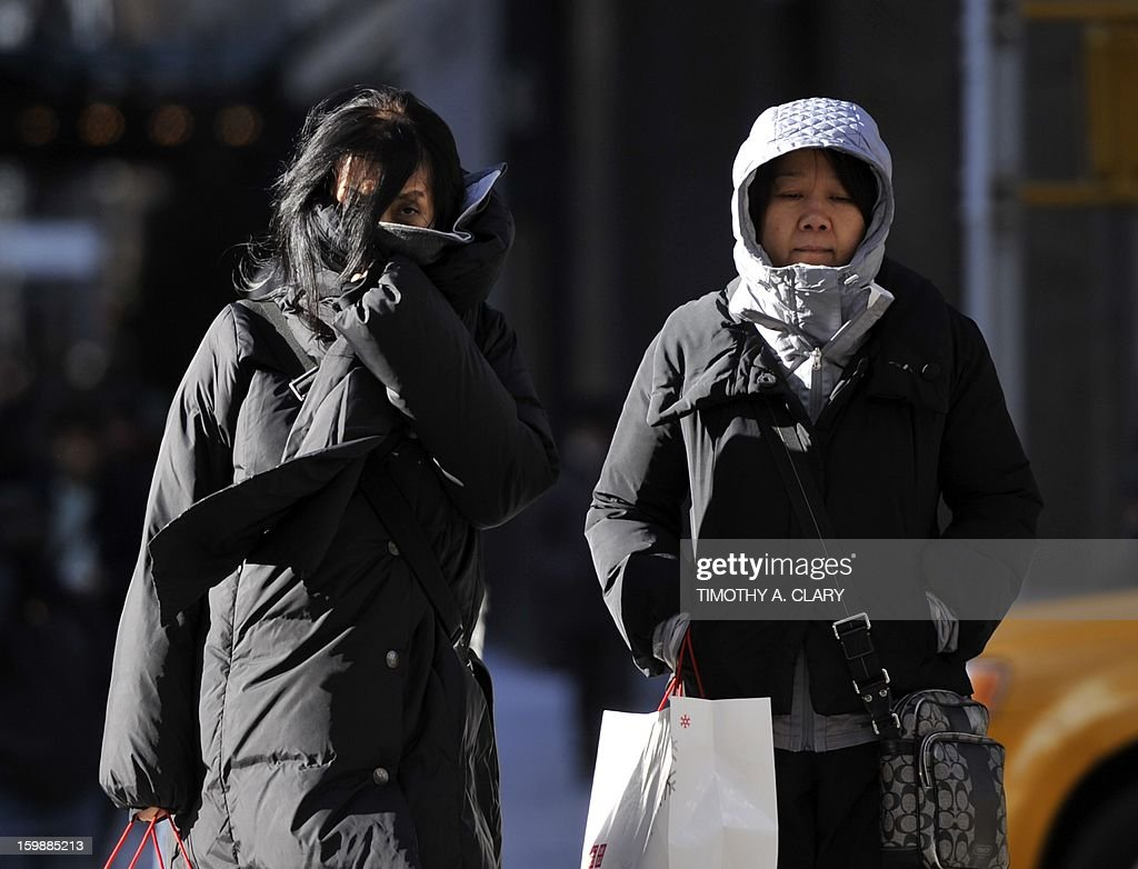 New Yorkers bundle up as they deal with the blast of cold weather that hit the East Coast January 22, 2013 creating bone-chilling cold temperatures. An Arctic blast gripped the US Midwest and Northeast on Tuesday, with winds pushing down the mercury to feel like 50 degrees Fahrenheit below zero (minus 46 degrees Celsius) and enough snow and ice to cancel schools and make roads slick.