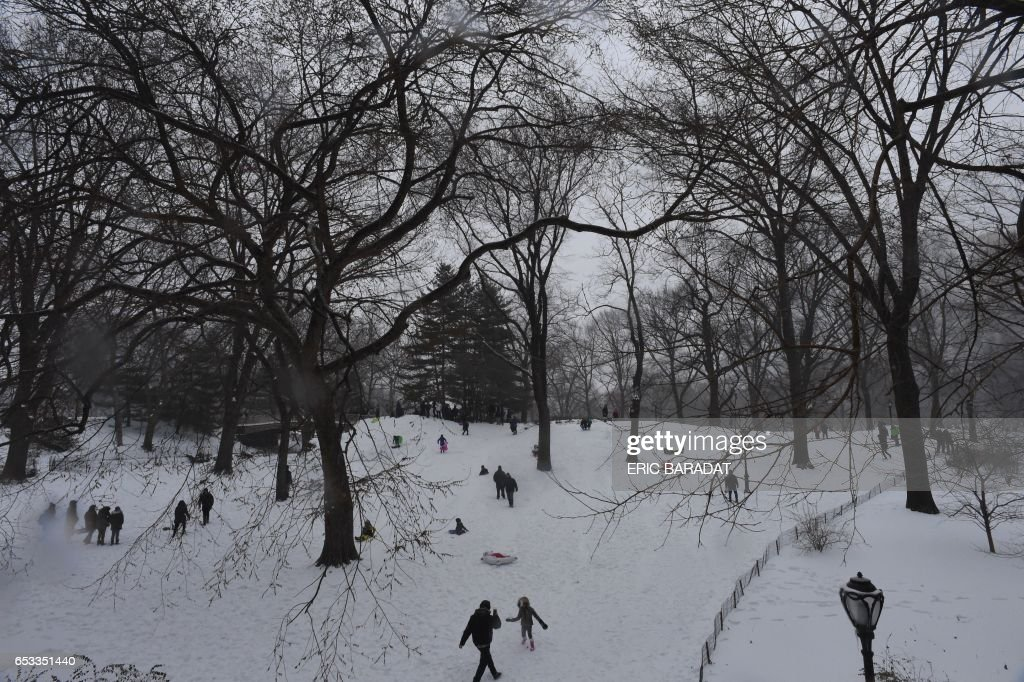 TOPSHOT - New Yorkers play on a snow-covered hill in Central Park in New York on March 14, 2017. Winter Storm Stella dumped sleet and snow across the northeastern United States on Tuesday but spared New York from the worst after authorities cancelled thousands of flights and shut schools. Blizzard warnings were in effect in parts of Connecticut, Massachusetts and upstate New York, but were lifted for New York City, the US financial capital home to 8.4 million residents, where snow turned to sleet, hail and rain. BARADAT