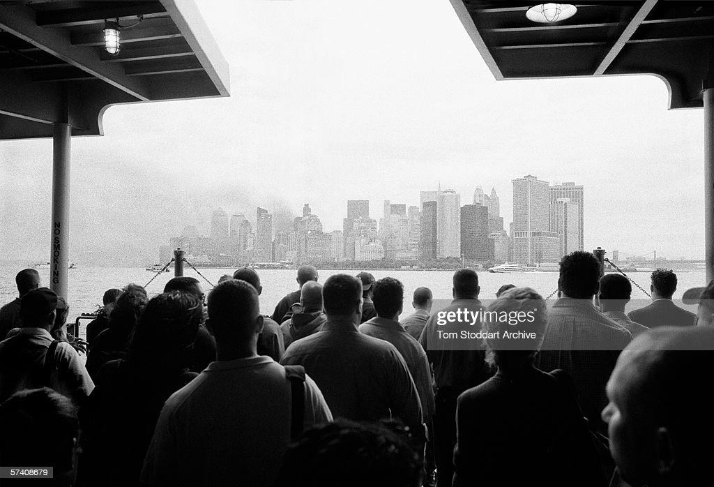 New Yorkers stand motionless and silent onboard the first Staten Island ferry to approach Manhattan after the World Trade Center attack of 9/11, 17th September 2001.