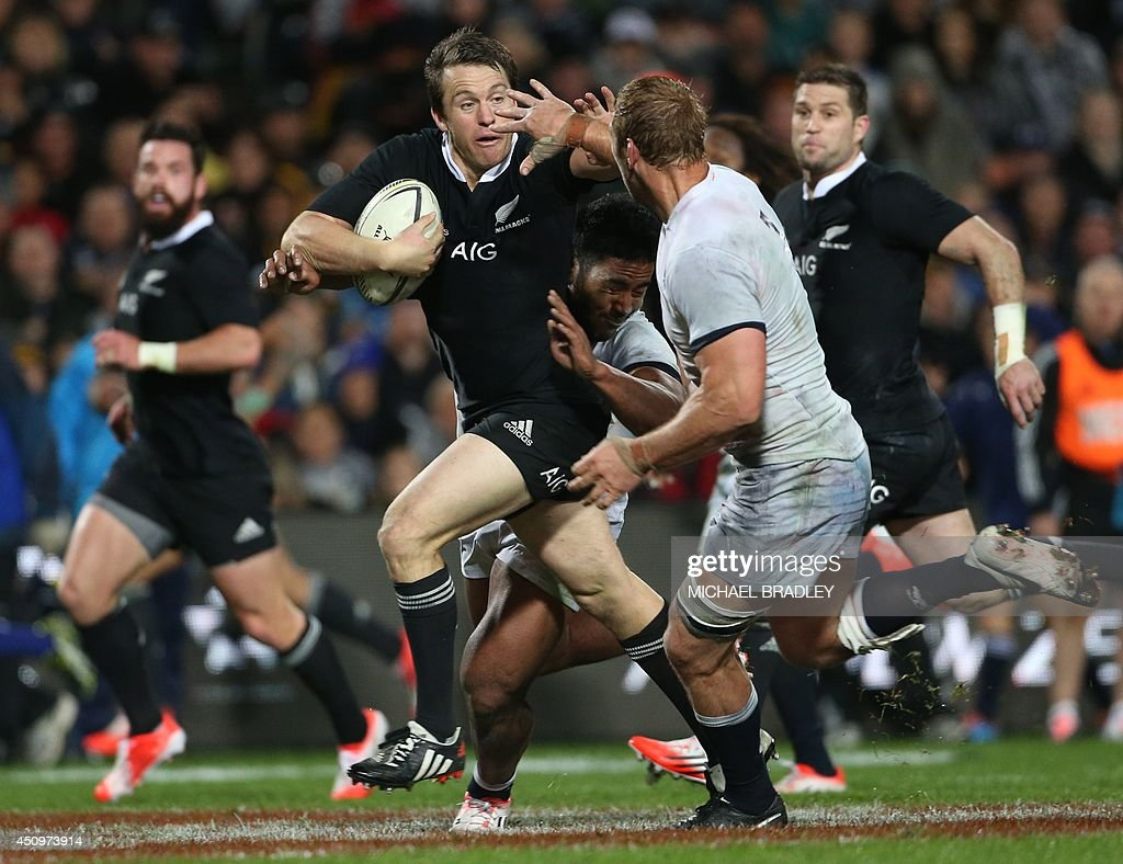 New Zealand All Blacks fullback Ben Smith (C) is tackled by England's Manusamoa Tuilagi (2nd-R) and Chris Robshaw (R) during the third rugby union test match in Hamilton on June 21, 2014. AFP PHOTO / Michael Bradley
