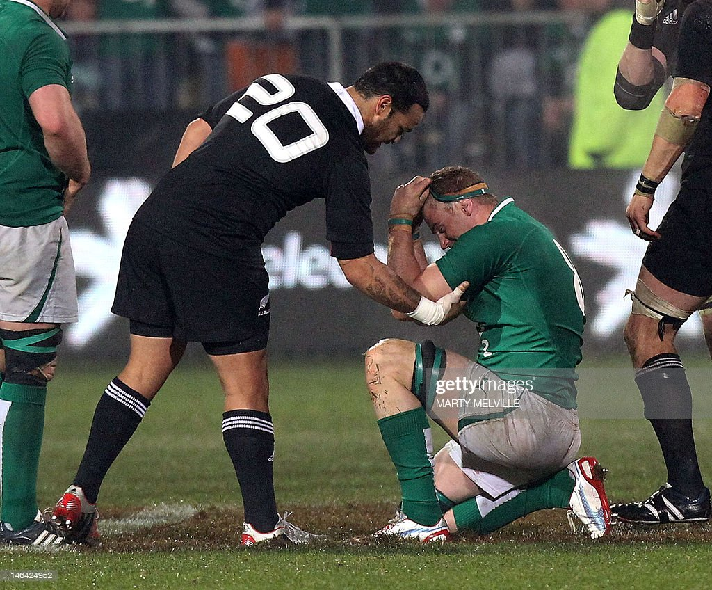 New Zealand All Blacks player Piri Weep (2nd-L) helps a dejected Jamie Heaslip of Ireland after the All Backs' win during their rugby union match at AMI Stadium in Christchurch on June 16, 2012. The All Blacks beat Ireland 22-19 in the second rugby Test. AFP PHOTO / Marty Melville