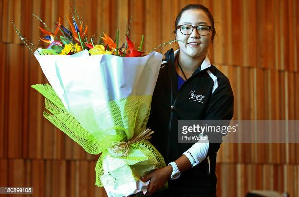 New Zealand amateur golfer Lydia Ko holds a bouquet of flowers following her arrival at Auckland International Airport on September 18 2013 in...