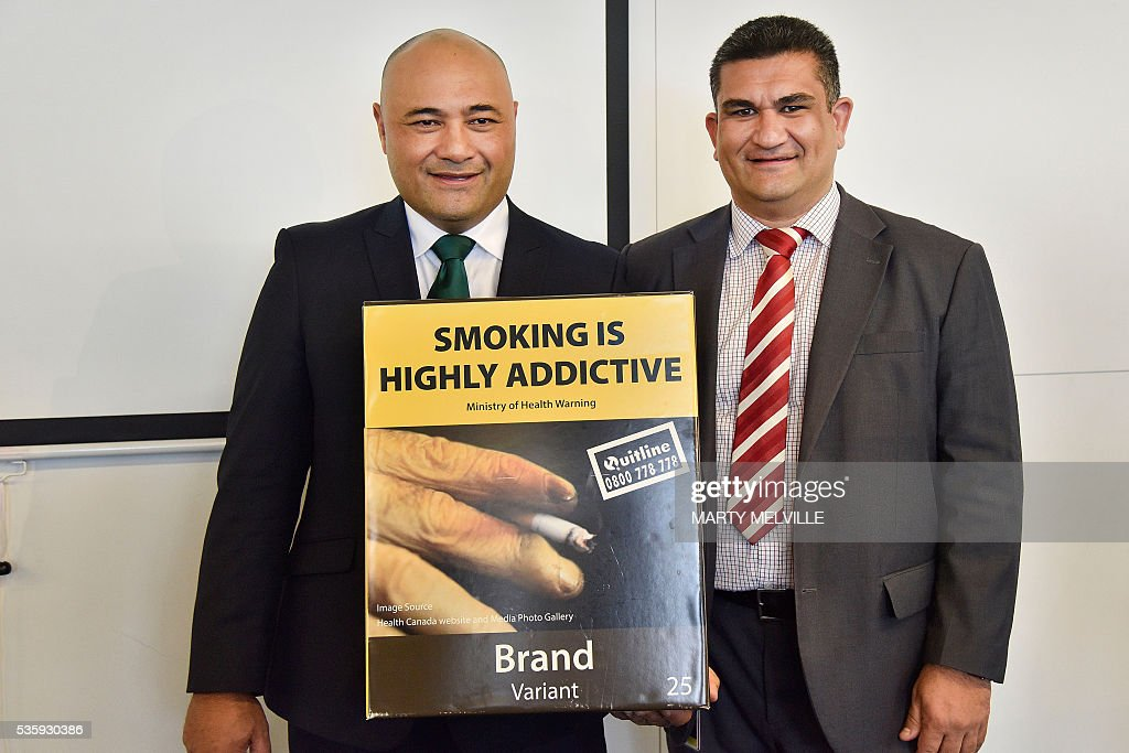 New Zealand Associate Health Minister Sam Lotu-Iiga (L) and Wellington City councillor Paul Eagle hold the mock-up of the new plain cigarette packaging during an announcement in Wellington on May 31, 2016. New Zealand said it will introduce plain packaging on tobacco products, joining a growing list of countries planning similar measures despite the threat of legal action from the industry. / AFP / Marty Melville
