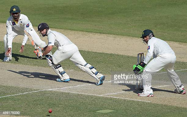 New Zealand batsman BJ Watling plays a shot as Pakistani wicketkeeper Sarfraz Ahmed and teammate Shan Masood look on during the second day of the...