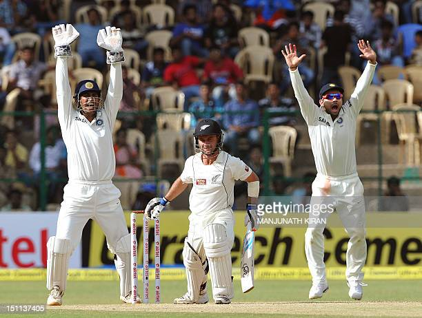 New Zealand batsman Kruger van Wyk reacts as Indian captain and wicketkeeper Mahendra Singh Dhoni and fielder Virat Kohli appeal to the umpire for a...