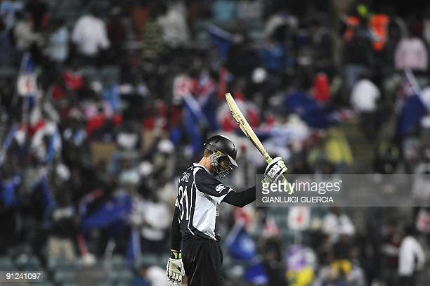 New Zealand batsman Martin Guptill raises his bat as he celebrates scoring 50 runs on September 29 2009 during the ICC Champions Trophy cricket match...