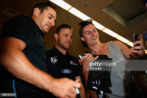 New Zealand Blackcaps captain Brendon McCullum and Nathan McCullum pose with fans after arriving at Auckland Airport on March 31 2015 in Auckland New...